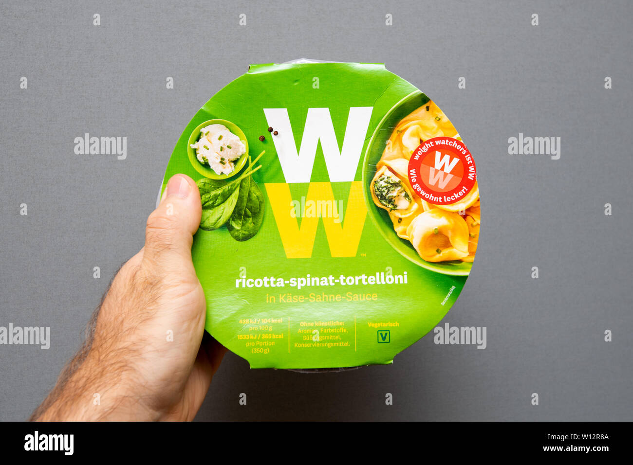 Paris, France - May 19, 2019: Man hand holding Weight Watchers Ricotta Spinach and Tortellini with cheese sauce - isolated gray background - Stock Image