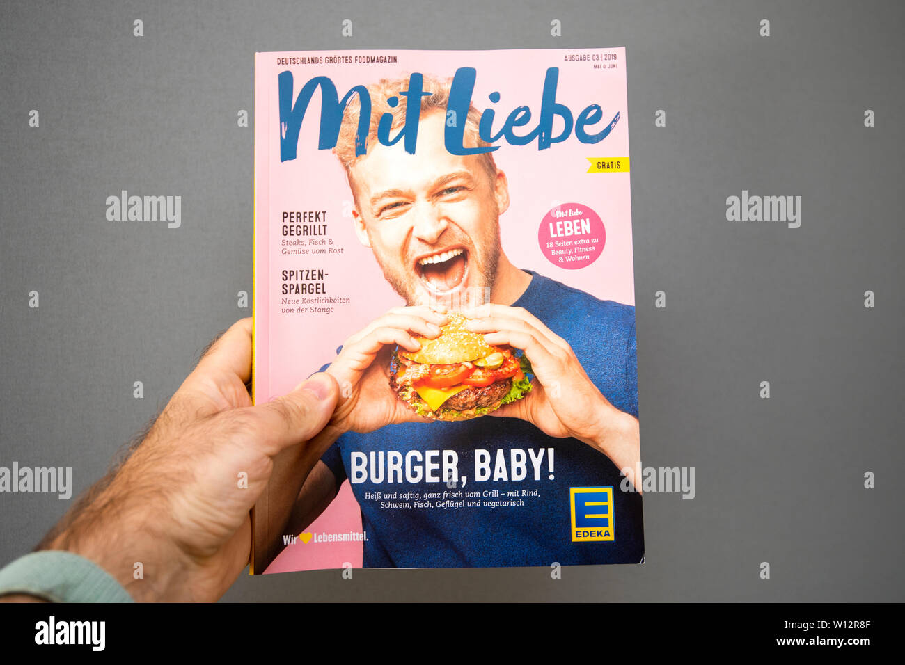 Paris, France - May 19, 2019: Man hand holding Mit Liebe magazine published by Edeka Supermarket featuring happy man eating a delicious hamburger - Stock Image