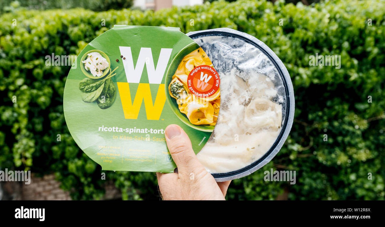 Paris, France - May 19, 2019: Man hand holding Weight Watchers Ricotta Spinach and Tortellini with cheese sauce green garden background - Stock Image