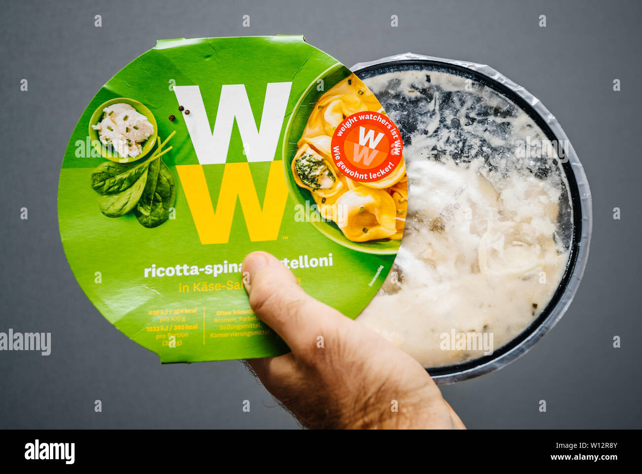 Paris, France - May 19, 2019: Man hand holding Weight Watchers Ricotta Spinach and Tortellini with cheese sauce gray background - Stock Image