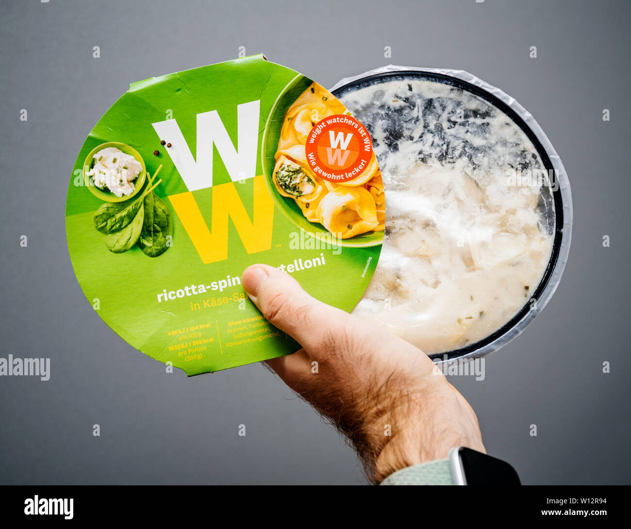 Paris, France - May 19, 2019: Man hand holding Weight Watchers Ricotta Spinach and Tortellini with cheese sauce gray isolated background - Stock Image