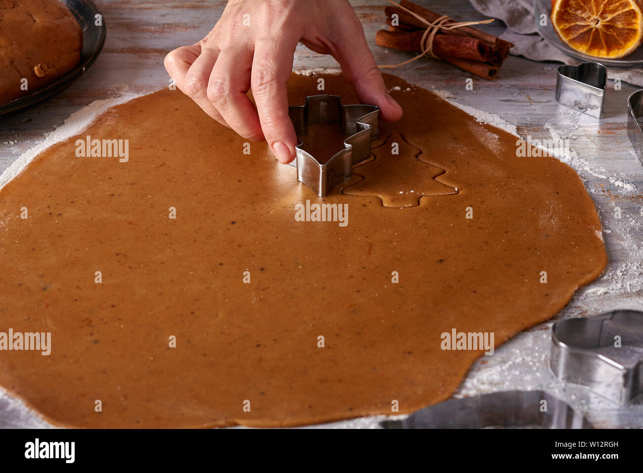 Woman's hands make gingerbread cookies shapes from dough - Stock Image