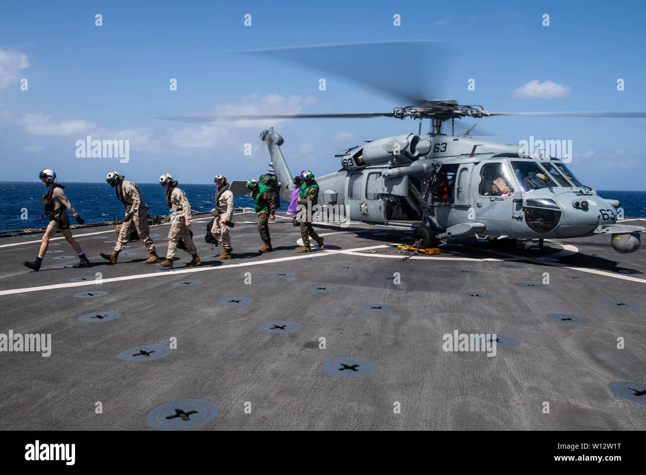 190624-N-HD110-0112  INDIAN OCEAN (June 24, 2019) U.S. Marines with the 11th Marine Expeditionary Unit exit an MH-60S Sea Hawk helicopter, assigned to Helicopter Sea Combat Squadron (HSC) 21, on the flight deck of the amphibious dock landing ship USS Harpers Ferry (LSD 49). Harpers Ferry is part of the Boxer Amphibious Ready Group and 11th MEU and is deployed to the U.S. 5th Fleet area of operations in support of naval operations to ensure maritime stability and security in the Central Region, connecting the Mediterranean and the Pacific through the western Indian Ocean and three strategic cho Stock Photo