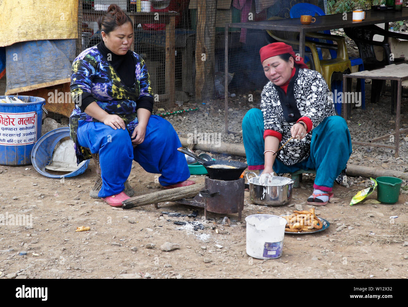 697d533b8 Women in traditional dress making sel (fried dough) at a roadside  restaurant in rural