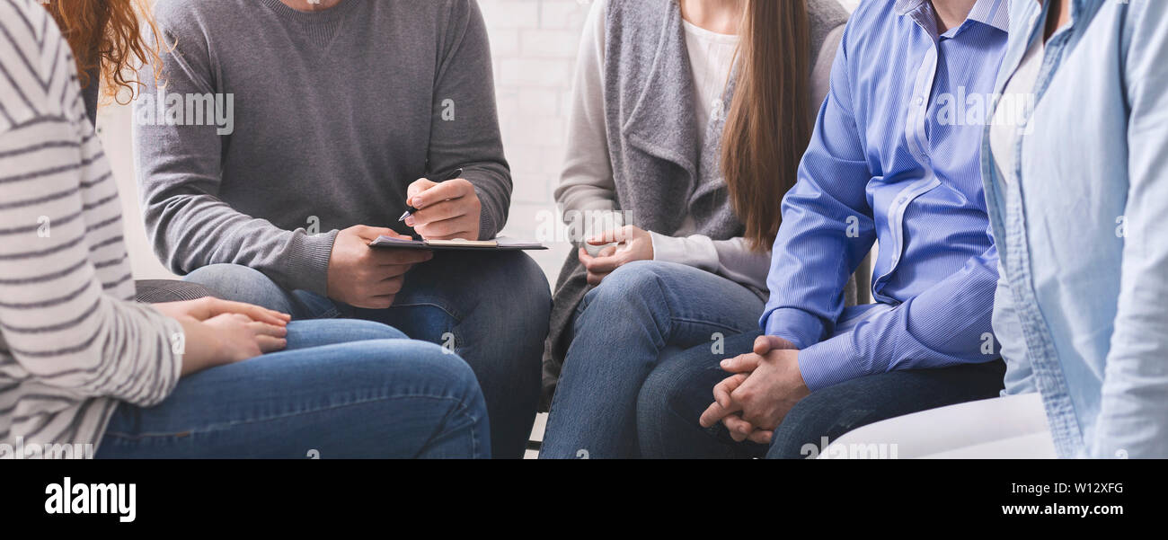 Counselor with clipboard talking to patients during group therapy Stock Photo