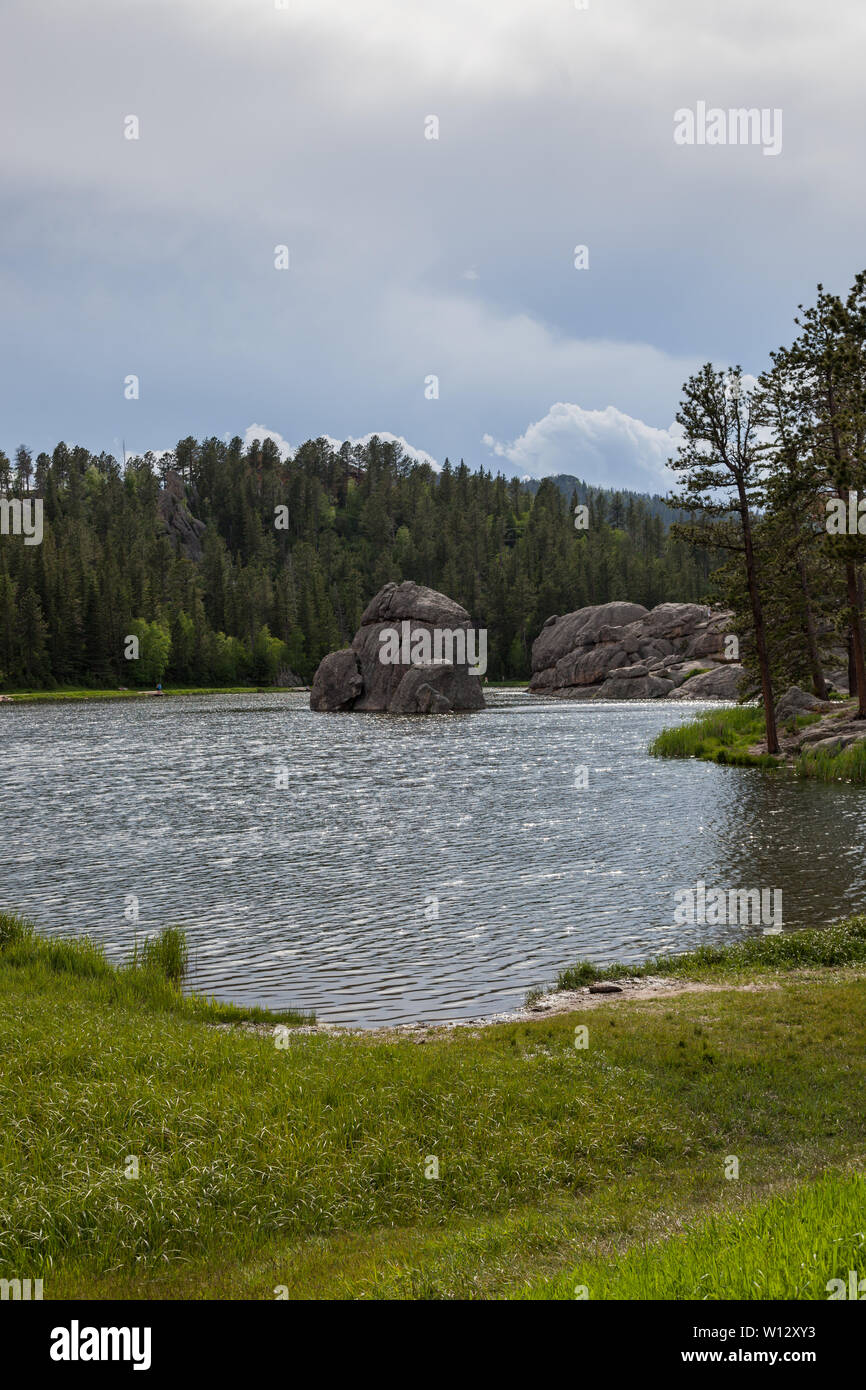 Large granite rock formations and trees along the shoreline of  Sylvan Lake in South Dakota. - Stock Image