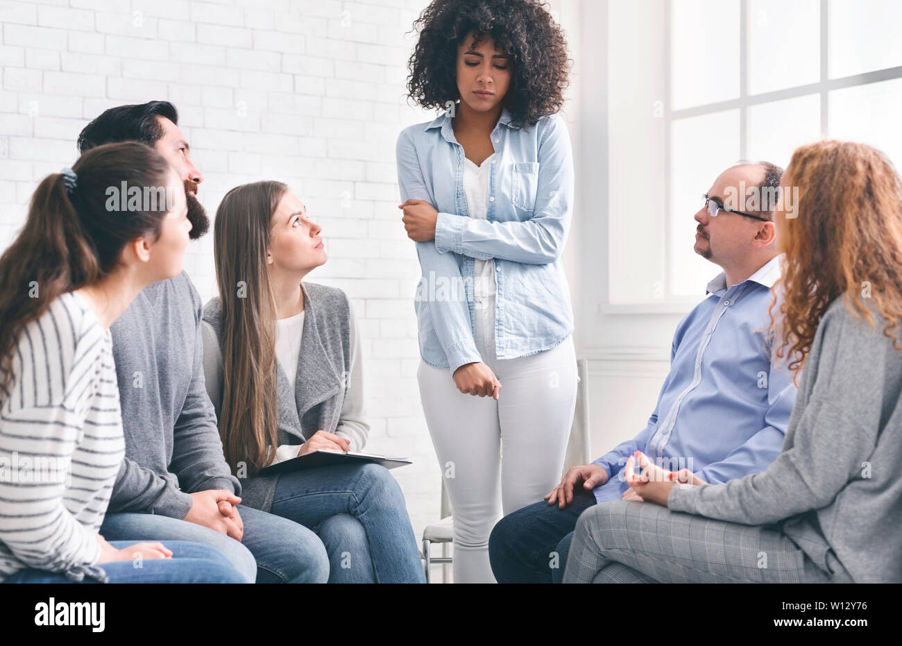 Rehab group listening to stressed woman standing up Stock Photo