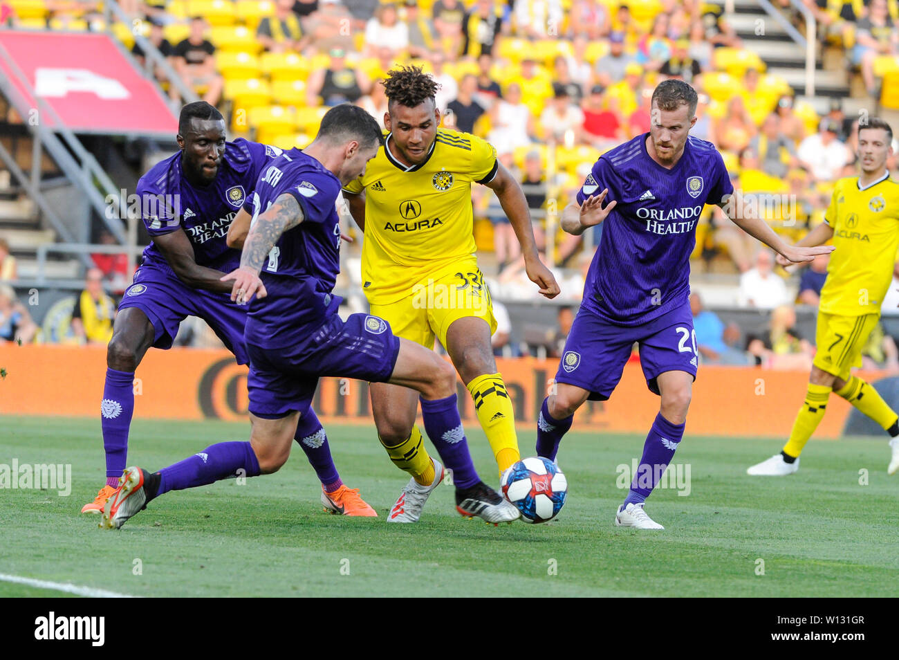 Saturday, June 29, 2019: Columbus Crew SC forward JJ Williams (33) tries to control the ball with Orlando City defender Kyle Smith (24), midfielder Oriol Rosell (20), and defender Lamine Sane (22) close by in the first half of the match between Orlando City and Columbus Crew SC at MAPFRE Stadium, in Columbus OH. Mandatory Photo Credit: Dorn Byg/Cal Sport Media. Orlando City 1 - Columbus Crew SC 0 after the first half - Stock Image