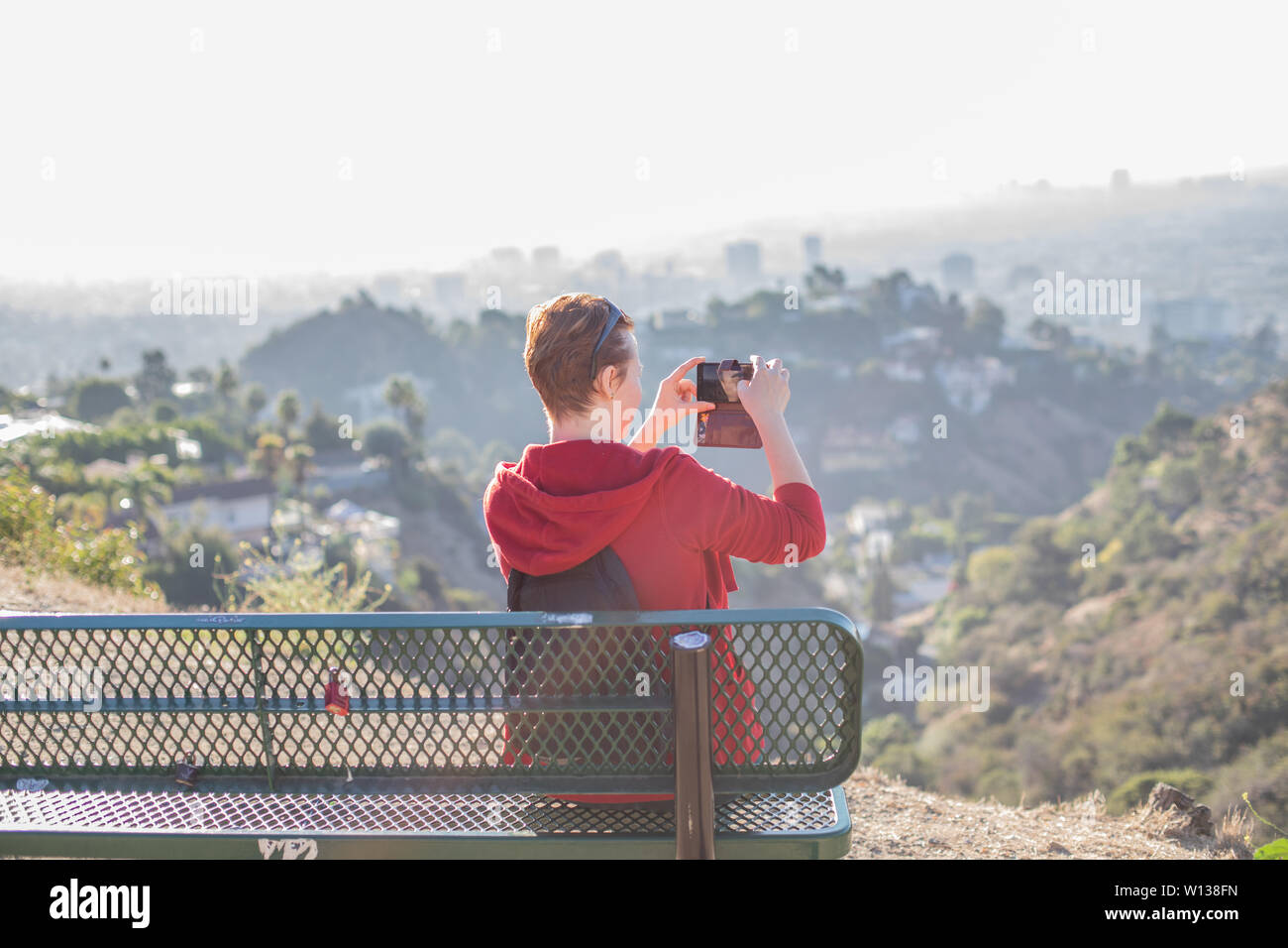 A young woman sitting on the bench on a hike and taking photos of the landscape, Los Angeles, California Stock Photo