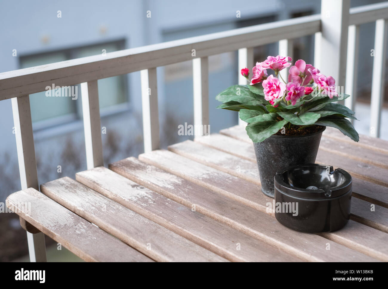 Pink flower with ceramic ashtray on wooden table at balcony - Stock Image