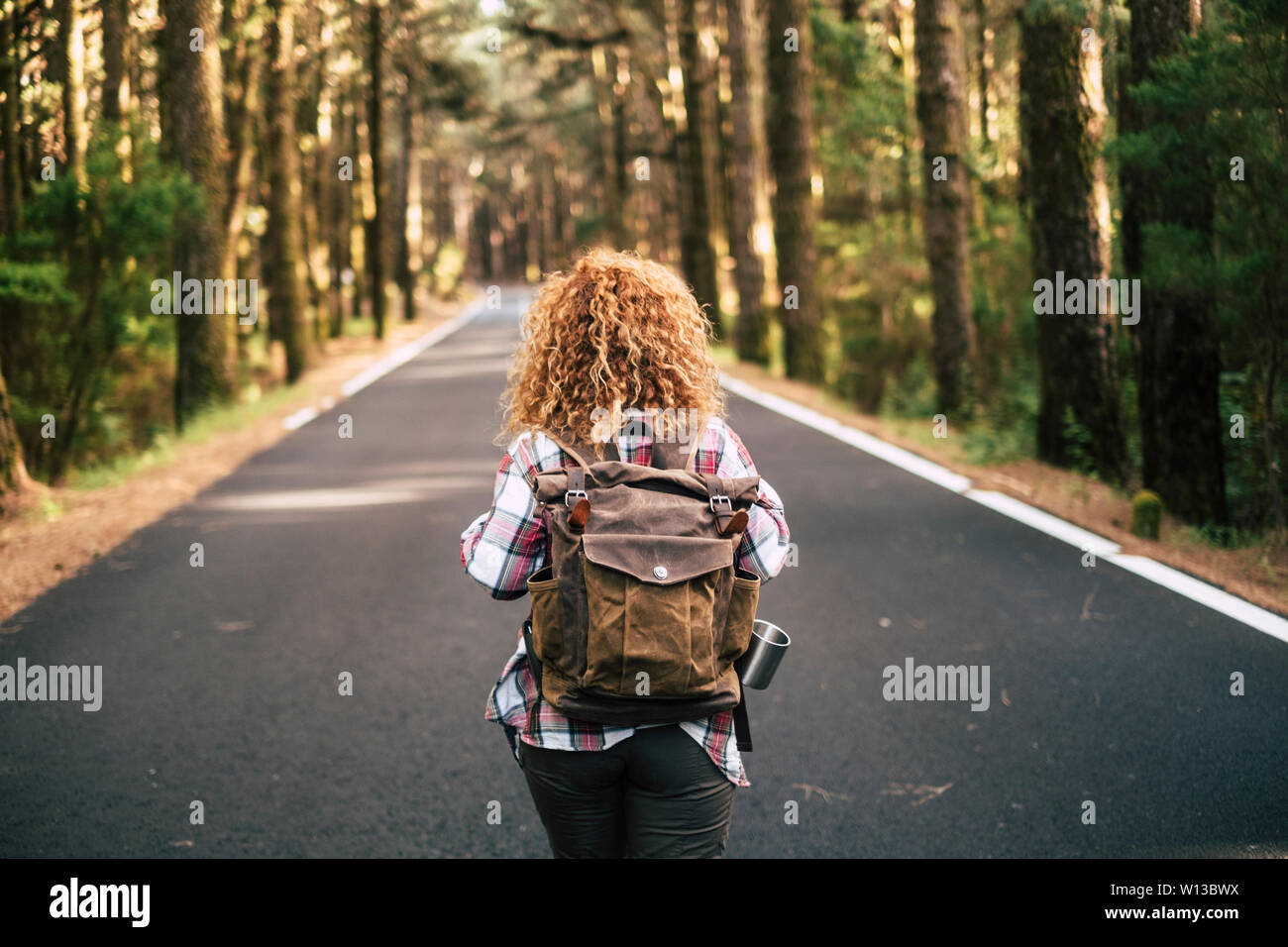 Rear view of alone woman curly hair walking in the street with backpack. Forest and mountain. Adventure and freedom concept Stock Photo