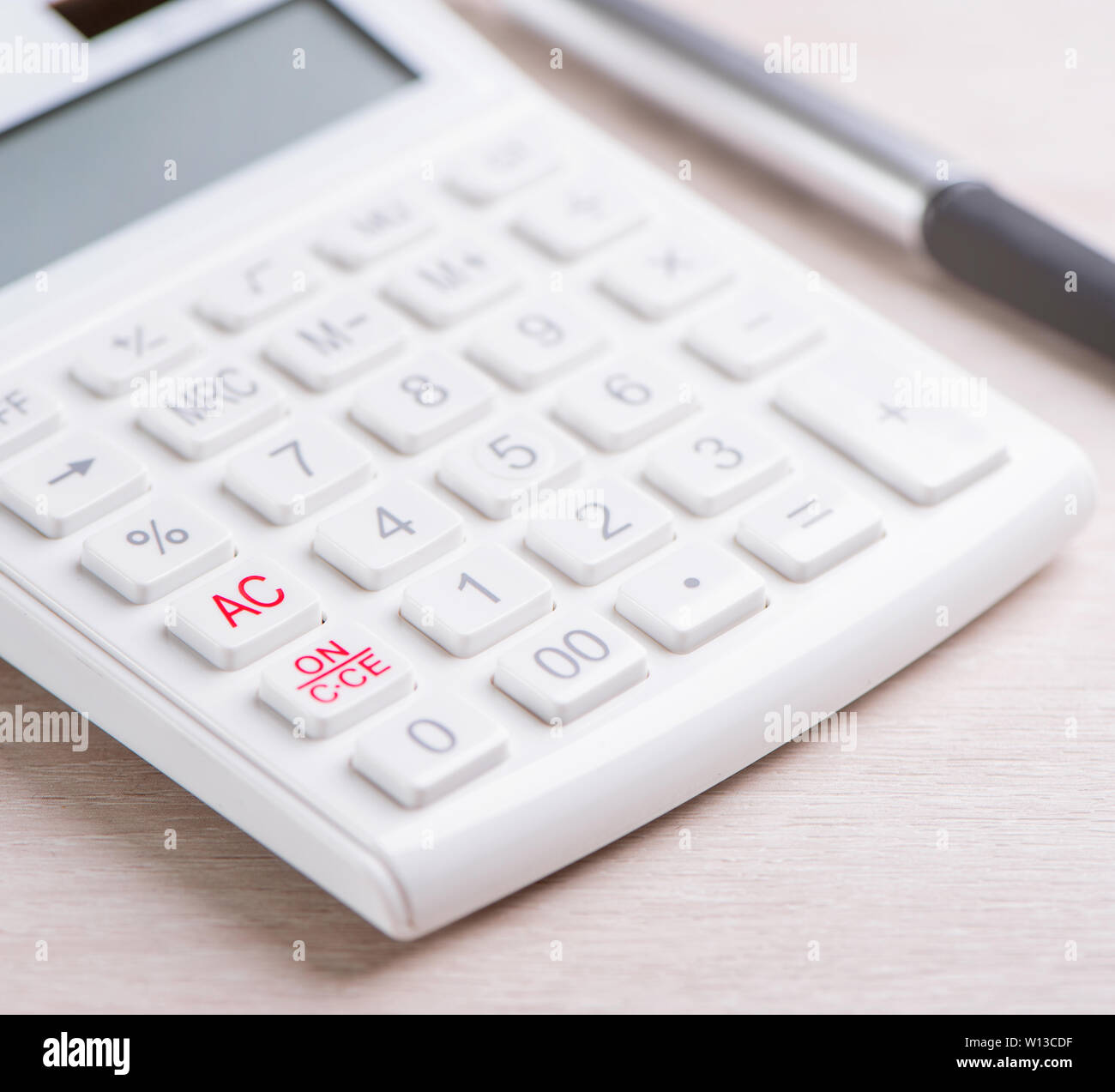 White calculator and pen on bright wooden table, analytics and statistics of financial profit, investment risk concept, copy space, macro, close up Stock Photo