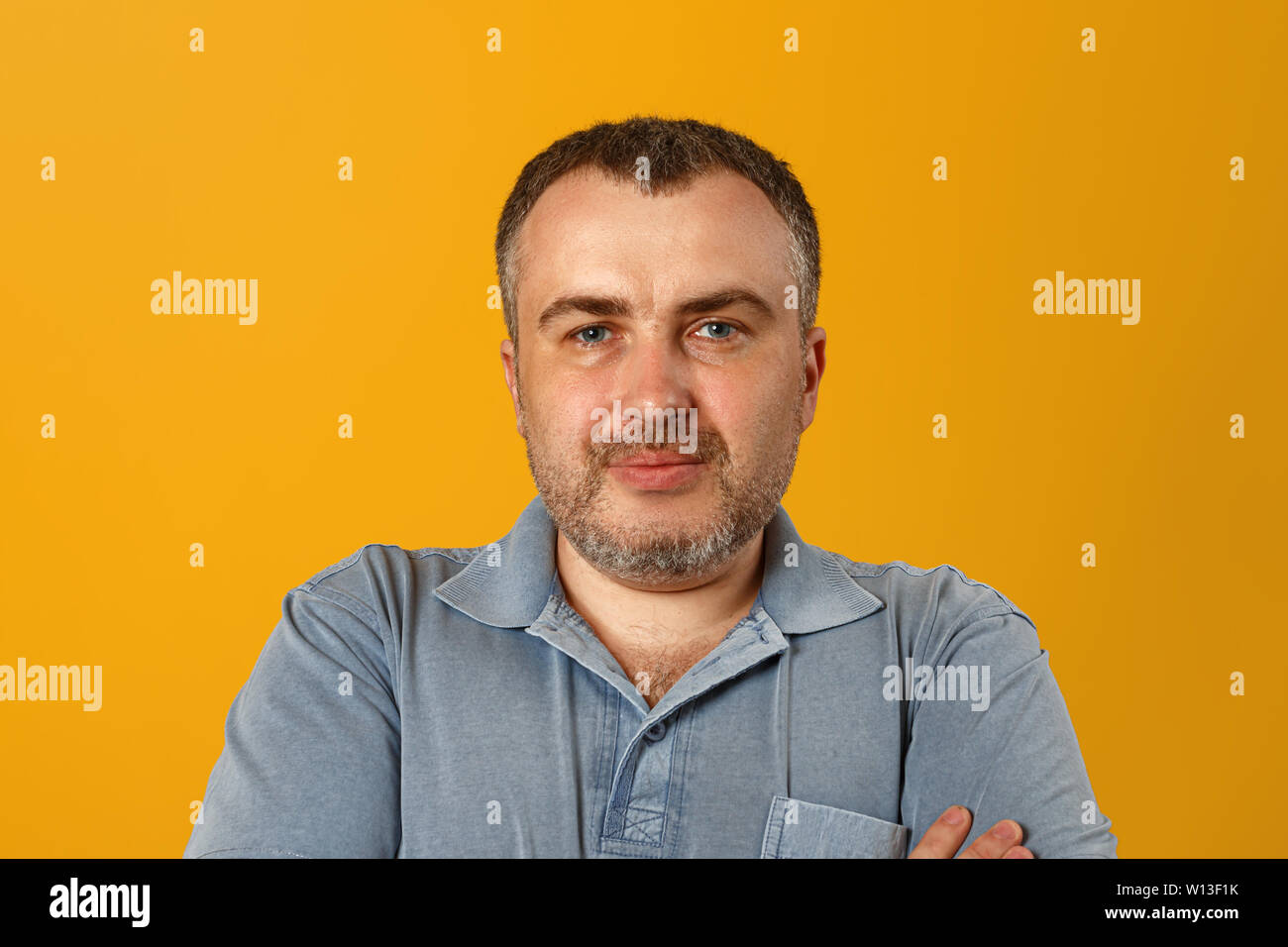 Serious man with folded arms and a deadpan expression posing in front of a yellow background. - Stock Image