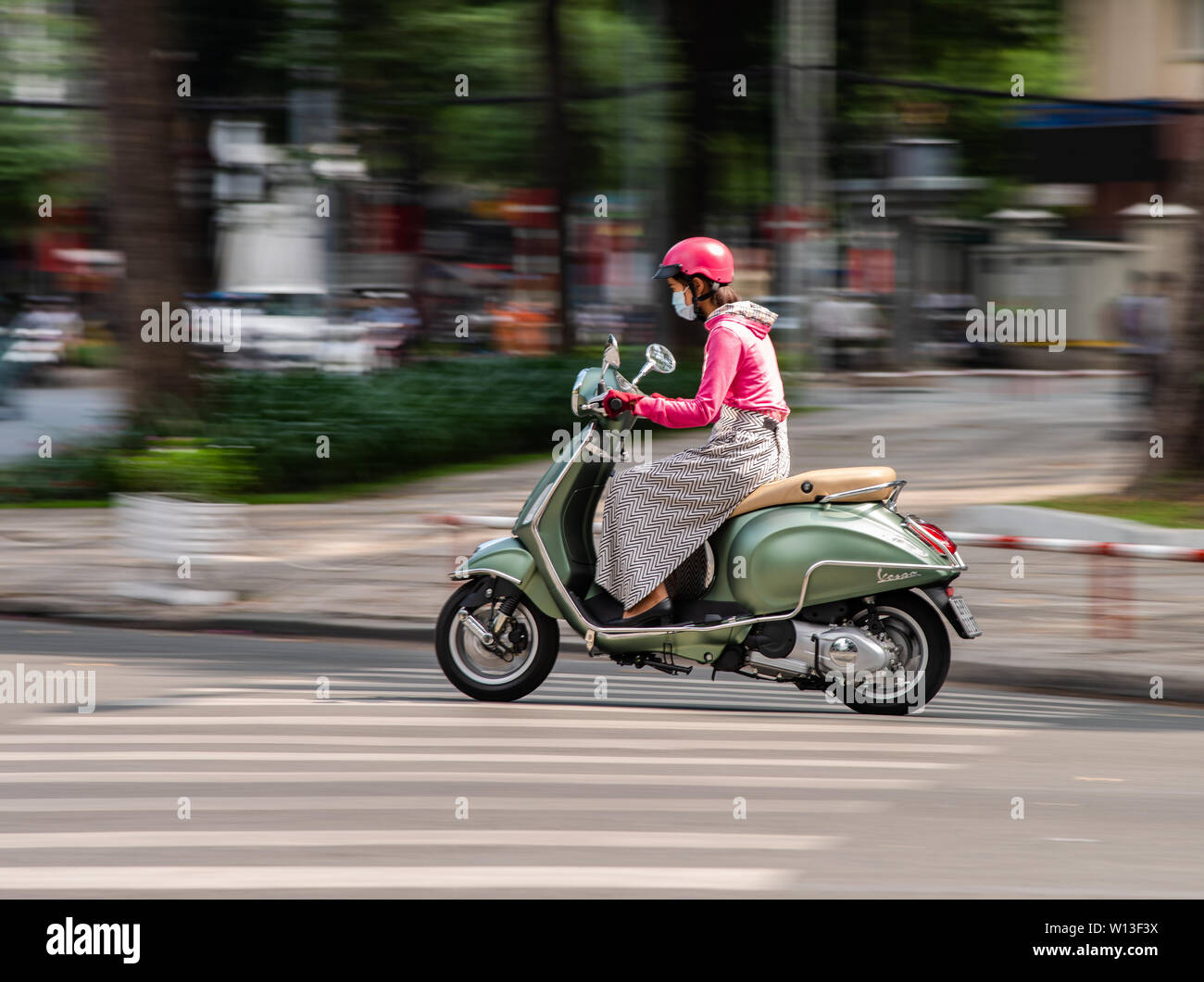 Ho Chi Minh City, Vietnam - January 11, 2016: Young woman driving her elegant Vespa scooter in downtown Ho Chi Minh City. - Stock Image