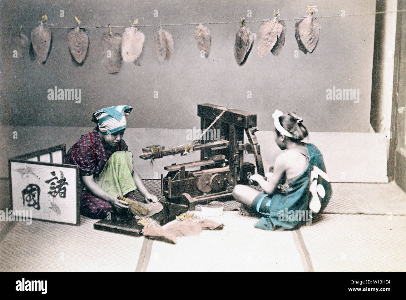 [ 1870s Japan - Japanese Tobacco Makers ] —   A woman and a man in traditional Japanese clothing are cutting tobacco leaves. The man is using a machine. The woman is brushing a leave with a small hand brush. A small screen can be seen on her left. In the background, tobacco leaves are hanging from a string.  19th century vintage albumen photograph. - Stock Image