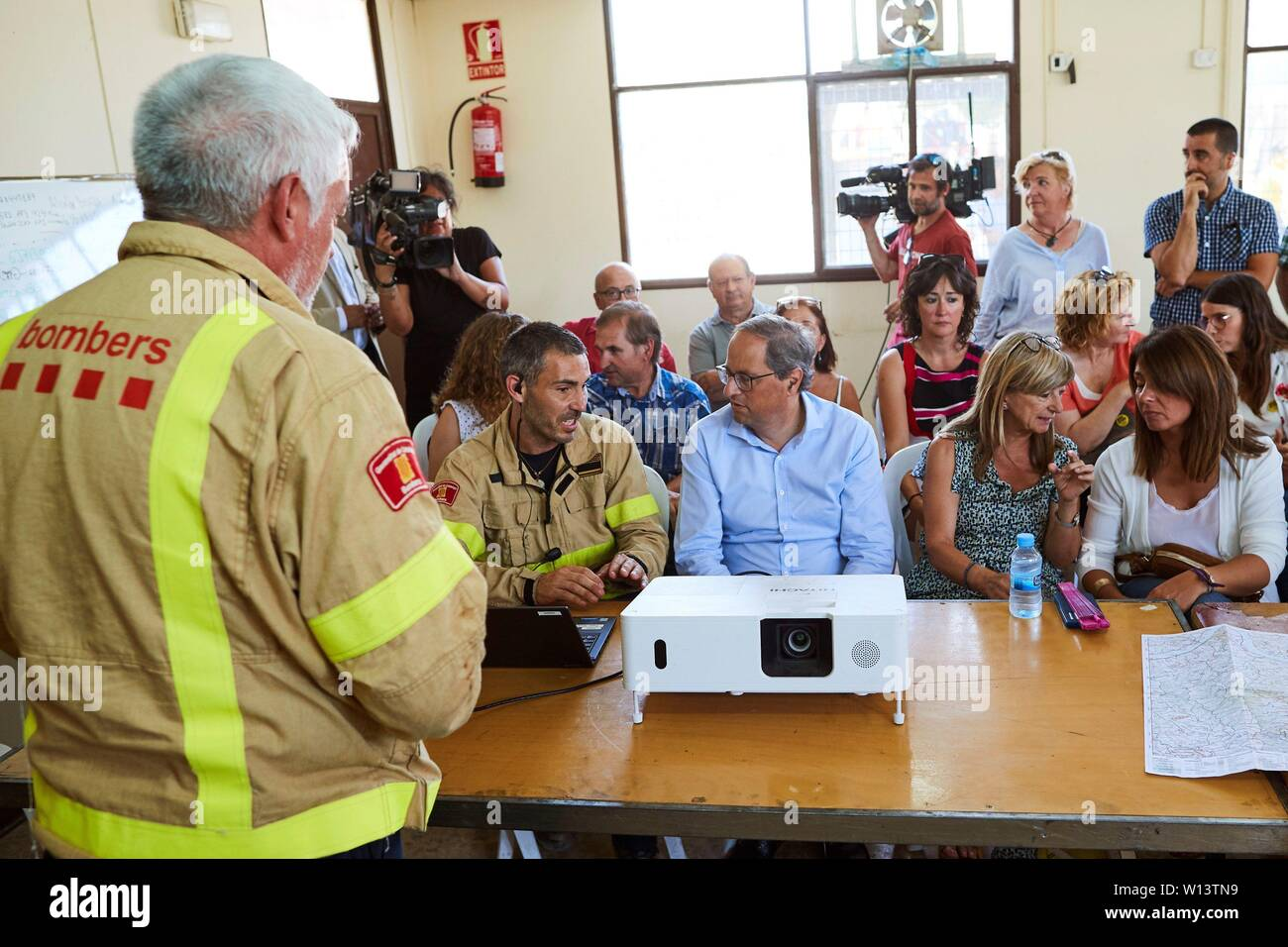 Tarragona, Spain. 30th June, 2019. Catalan regional President, Quim Torra (C), chats with firefighters as he meets mayors of towns in Ribera d'Ebre local administrative division in Vinebre town, Tarragona, Spain, 30 June 2019, to analyze the situation that caused the fire declared 26 June 2019 that burnt more than 6,000 hectares of land. Credit: EFE News Agency/Alamy Live News - Stock Image