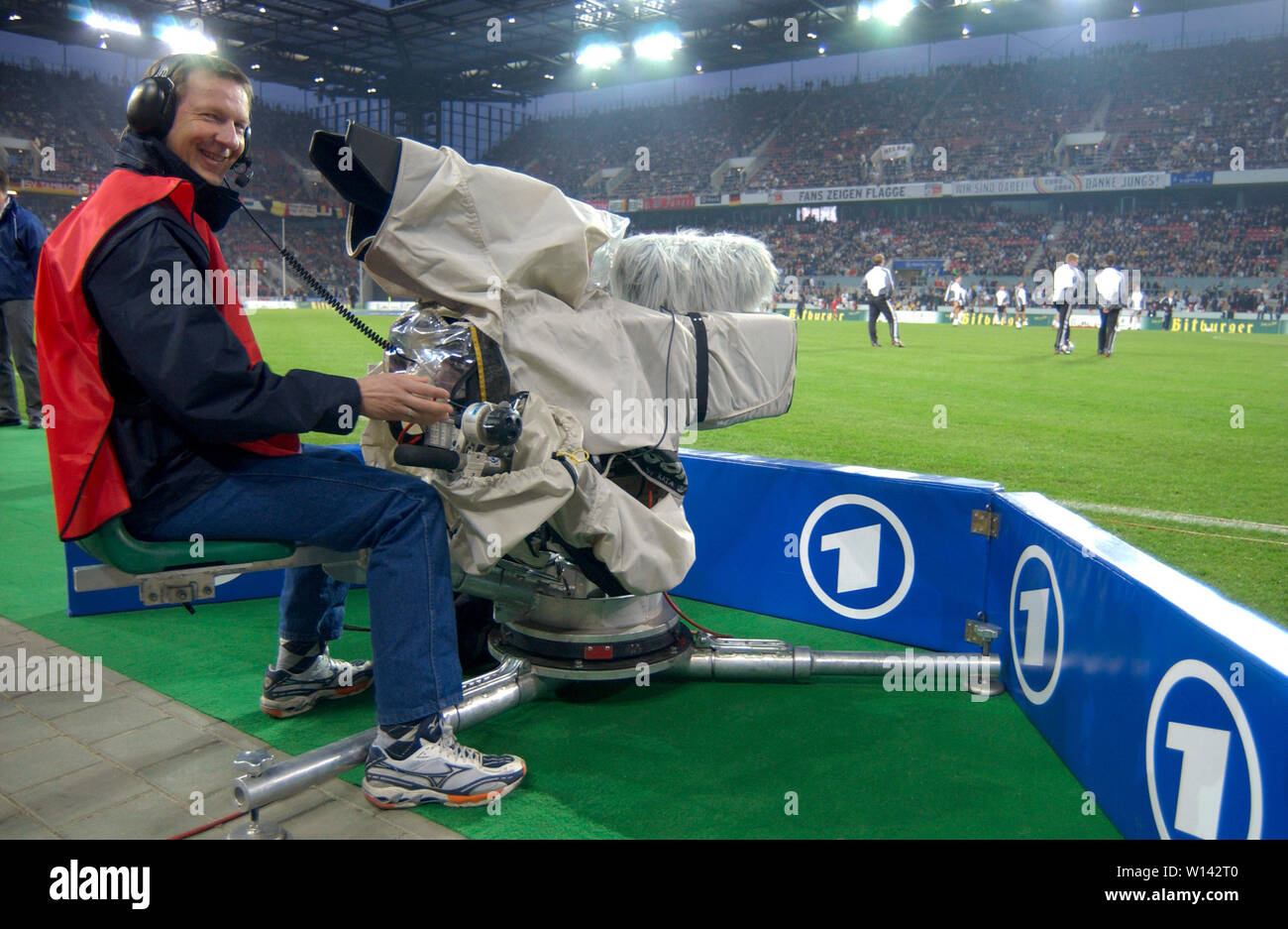 """Rhein-Energie-Stadion Cologne Germany, 31.3.2004, Football: International friendly, Germany (white) vs. Belgium (red) 3:0 --- TV cameraman of the German Television channel """"Das ERSTE"""" (ARD) on the sidelines of the pitch Stock Photo"""