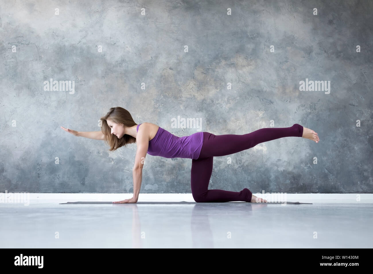 woman practicing yoga, standing in Bird dog pose, or tiger pose Stock Photo