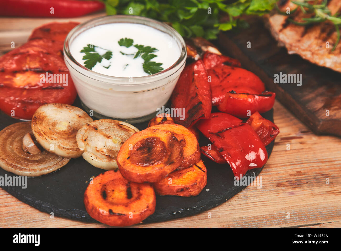 Grilled vegetables on black slate plate on wooden background. view from above. Diet vegan food. Healthy. Top view. Frame. Flat lay. Copy space. - Stock Image