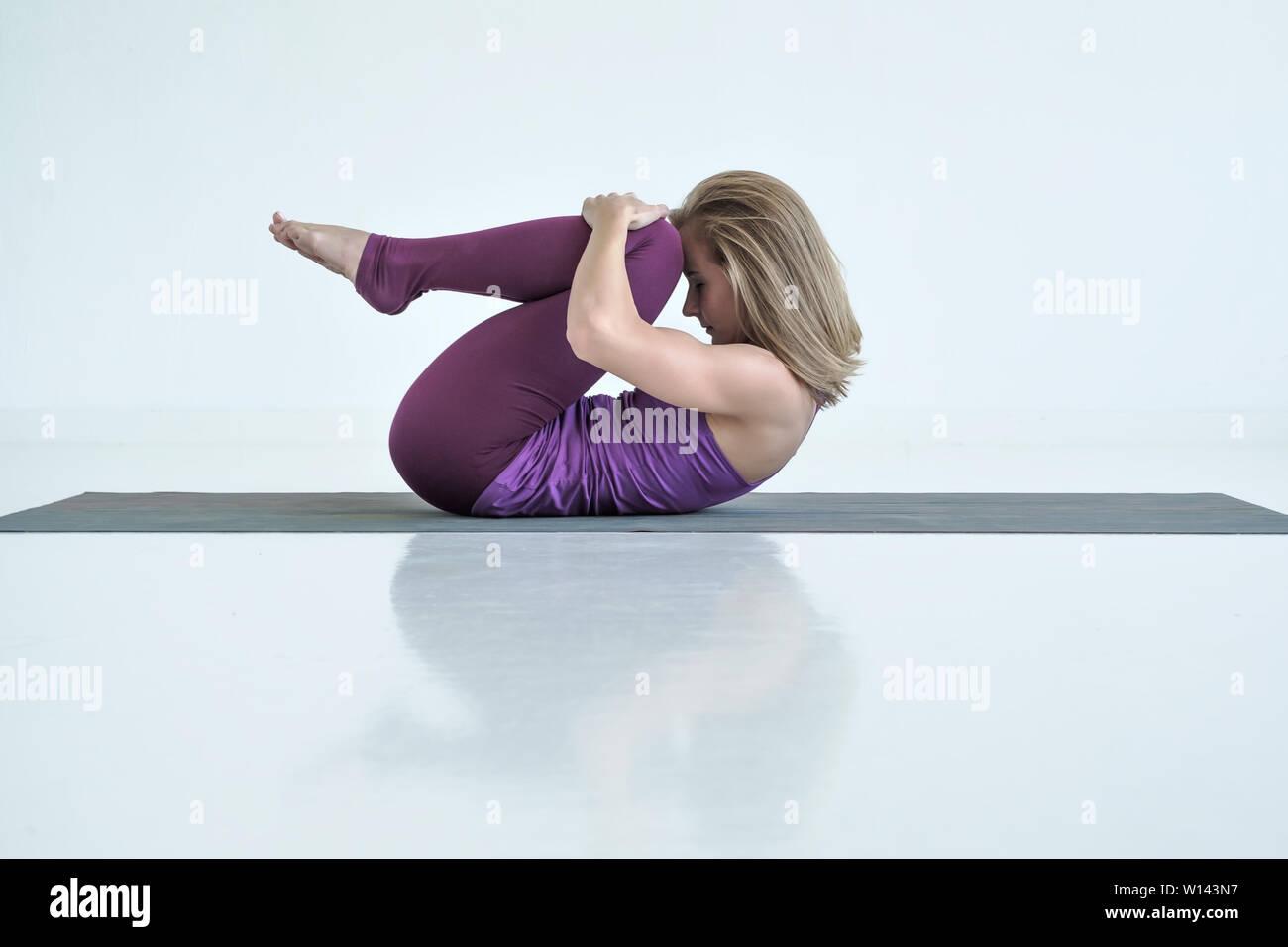 Woman practicing yoga, doing Knees to Chest exercise, Apanasana pose. - Stock Image