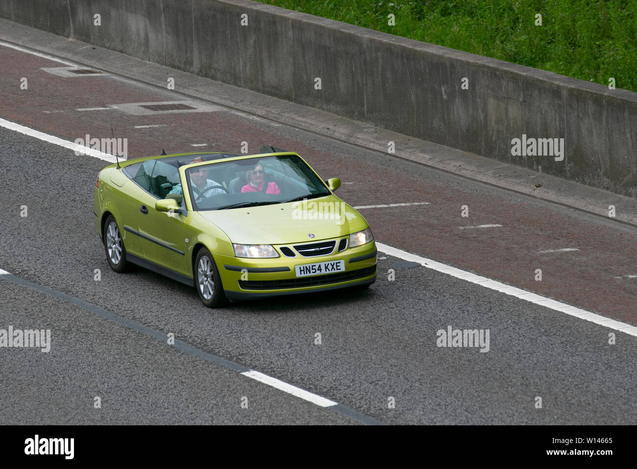 2004 yellow Saab 9-3 Linear 150 BHP S-A; M6, Lancaster, UK; Vehicular traffic, transport, modern, saloon cars, north-bound on the 3 lane highway. - Stock Image