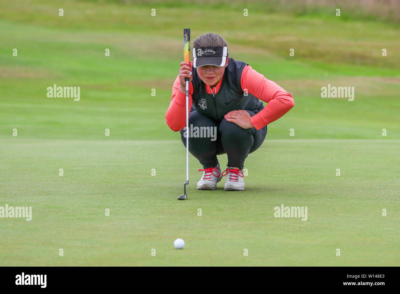 Troon, Scotland, UK. 30th June 2019. On the final day of the Competition the remaining 8 golfers, playing matchplay golf competed over Barassie Links Golf course, Troon in blustery wind and squally rain conditions to try and win the Championship Cup and the Clark Rosebowl. Image of ELLIE DOCHERTY epresenting Moray GC linng up a putt on the 14th green Credit: Findlay/Alamy Live News - Stock Image