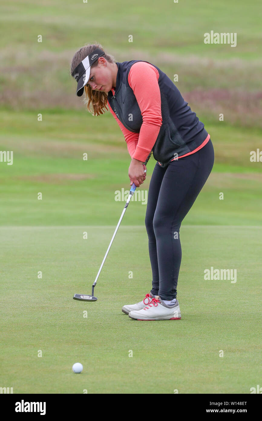 Troon, Scotland, UK. 30th June 2019. On the final day of the Competition the remaining 8 golfers, playing matchplay golf competed over Barassie Links Golf course, Troon in blustery wind and squally rain conditions to try and win the Championship Cup and the Clark Rosebowl. Image of ELLIE DOCHERTY epresenting Moray GC putting on the 14th green Credit: Findlay/Alamy Live News - Stock Image