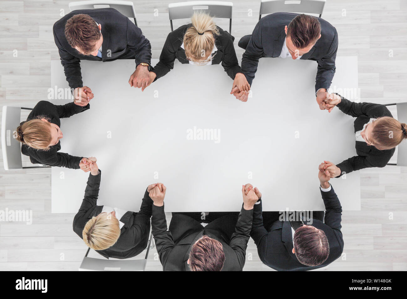 Business team holding hands sitting around the table, top view , copy space for text - Stock Image