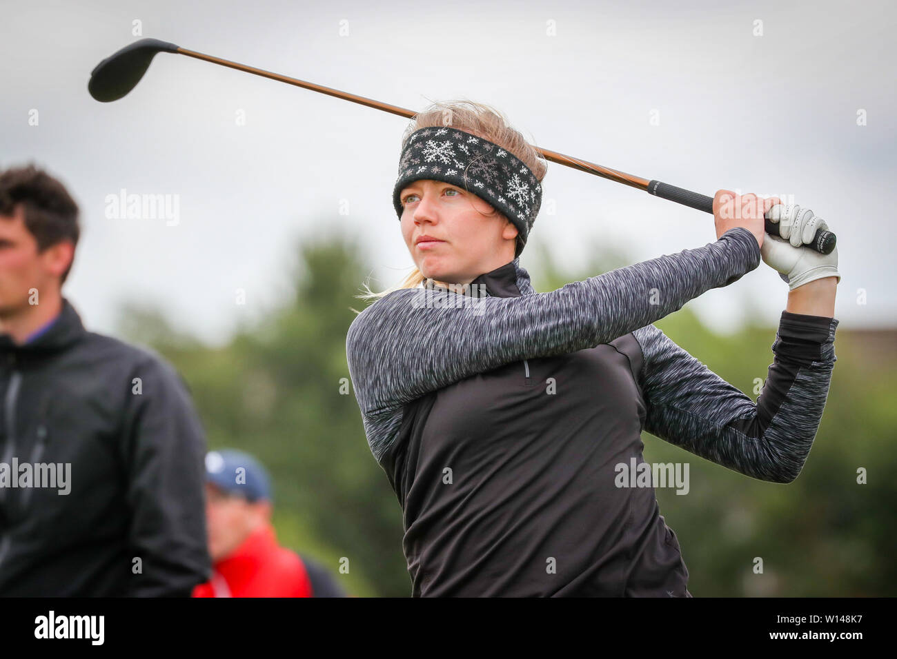 Troon, Scotland, UK. 30th June 2019. On the final day of the Competition the remaining 8 golfers, playing matchplay golf competed over Barassie Links Golf course, Troon in blustery wind and squally rain conditions to try and win the Championship Cup and the Clark Rosebowl. Image of KIMBERLEY BEVERIDGE representing Aboyne Golf club teeing off at the 15th Credit: Findlay/Alamy Live News - Stock Image