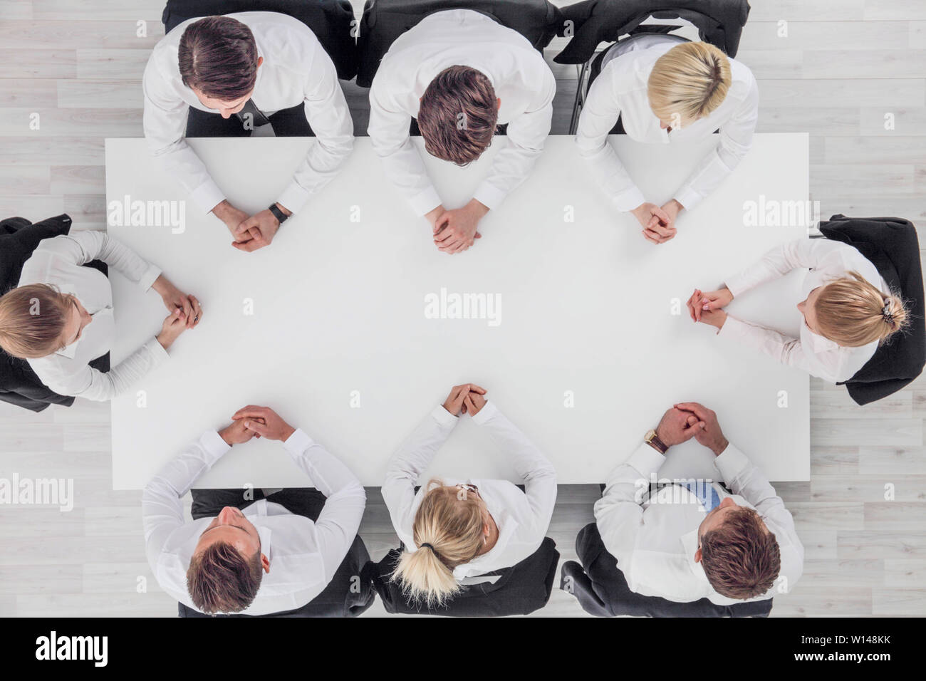 Business team sitting around white table, white copy space for text - Stock Image
