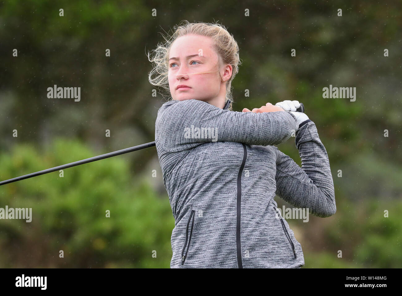 Troon, Scotland, UK. 30th June 2019. On the final day of the Competition the remaining 8 golfers, playing matchplay golf competed over Barassie Links Golf course, Troon in blustery wind and squally rain conditions to try and win the Championship Cup and the Clark Rosebowl.Image of KIMBERLEY BEVERIDGE representing Aboyne Golf club teeing off at the 17th Credit: Findlay/Alamy Live News - Stock Image