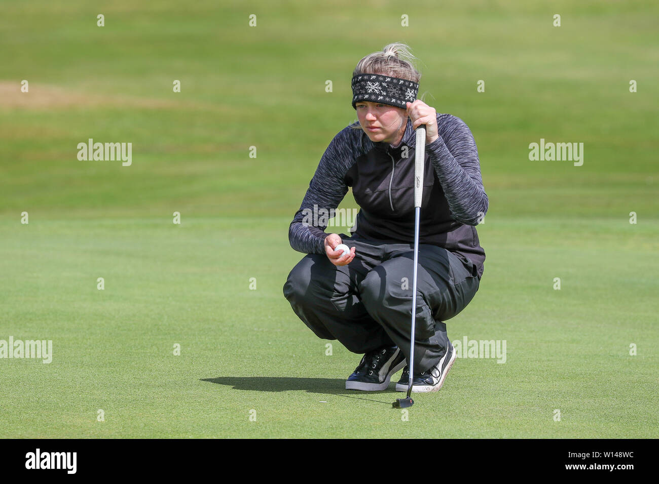 Troon, Scotland, UK. 30th June 2019. On the final day of the Competition the remaining 8 golfers, playing matchplay golf competed over Barassie Links Golf course, Troon in blustery wind and squally rain conditions to try and win the Championship Cup and the Clark Rosebowl. Image of KIMBERLEY BEVERIDGE representing Aboyne Golf club lining up a putt on the 14th green Credit: Findlay/Alamy Live News - Stock Image