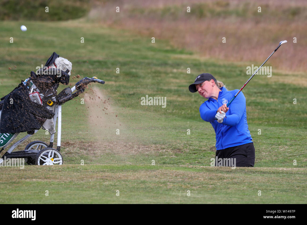 Troon, Scotland, UK. 30th June 2019. On the final day of the Competition the remaining 8 golfers, playing matchplay golf competed over Barassie Links Golf course, Troon in blustery wind and squally rain conditions to try and win the Championship Cup and the Clark Rosebowl. CHLOE GOADBY representing St Regulus Ladies Golf Club playing out the greenside bunker at the 16th Credit: Findlay/Alamy Live News - Stock Image