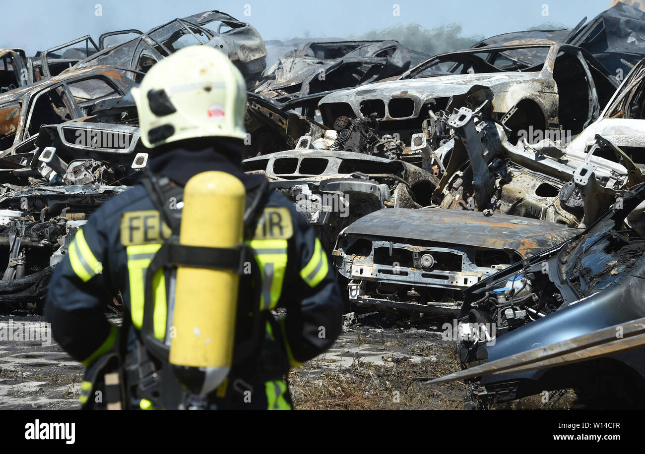 """Duvendiek, Germany. 30th June, 2019. Firefighters extinguish car wrecks after a major fire at a scrap yard near Niepars (Vorpommern-Rügen district) near Stralsund. About 500 car wrecks and tires had caught fire - how it came to the fire was still unclear, as the police reported. (to dpa """"About 500 burning car wrecks - cloud of smoke visible for miles"""") Credit: Stefan Sauer/dpa-Zentralbild/dpa/Alamy Live News Stock Photo"""