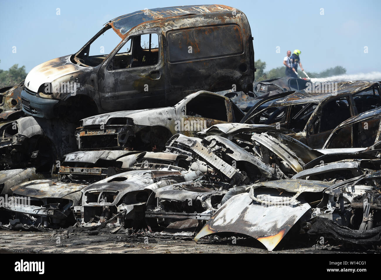 "Duvendiek, Germany. 30th June, 2019. Firefighters extinguish car wrecks after a major fire at a scrap yard near Niepars (Vorpommern-Rügen district) near Stralsund. About 500 car wrecks and tires had caught fire - how it came to the fire was still unclear, as the police reported. (to dpa ""About 500 burning car wrecks - cloud of smoke visible for miles"") Credit: Stefan Sauer/dpa-Zentralbild/dpa/Alamy Live News Stock Photo"