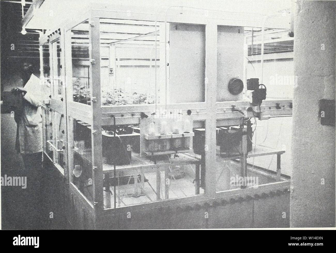 Archive image from page 12 of Design and operation of a. Design and operation of a carbon-14 biosynthesis chamber . designoperationo911smit Year: 1962  ±4 inches of water was created by a 3° F. tem- perature variation. A safety valve was designed to prevent greater fluctuations (fig. 10). The de- irice was composed of two vessels containing so- dium hydroxide solution to the level that pressure inside the chamber or outside would force air through the safety valve at a rate great enough to prevent dangerous pressure buildup. Air pass- ing through the trap was washed free of C02 and radioactivi - Stock Image