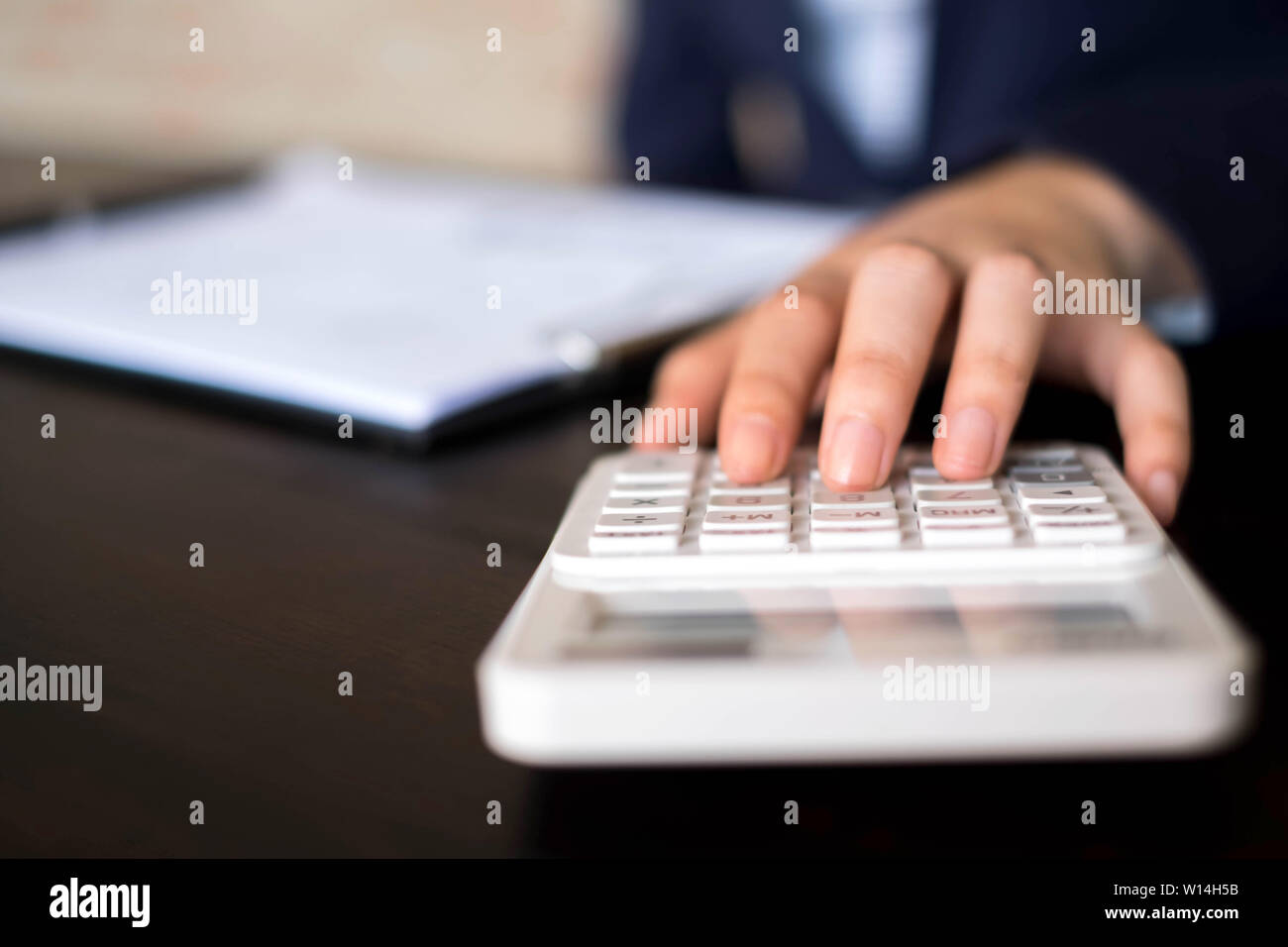 Businesswomen calculate the income from the export business on the wood table.Business concept. - Stock Image