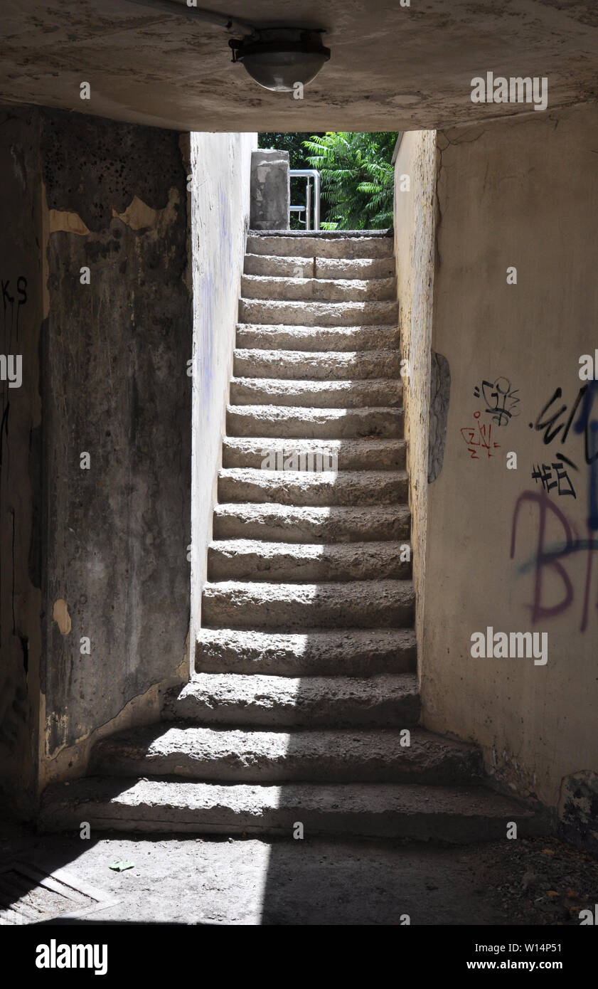 Ascending passage from underground area with contrast sunlight upstairs, weathered steps and narrow dirty concrete walls Stock Photo