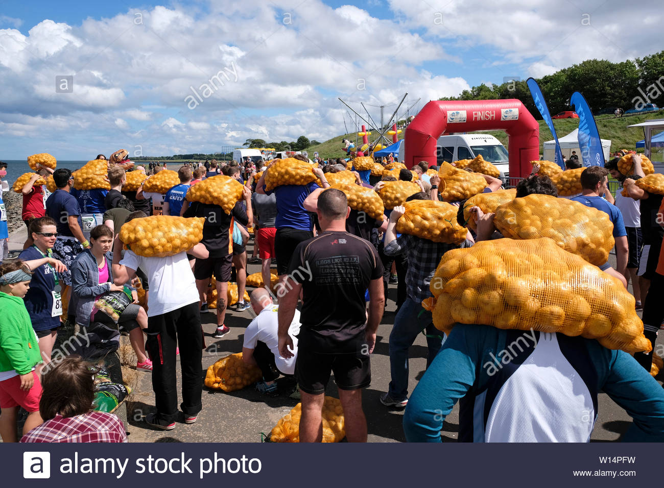 Edinburgh, Scotland, UK. 30th June 2019.  Participants with their bag of tatties gathering before competing in The Great Scottish Tattie Run at Silverknowes Promenade, organised by Great Scottish Events, a fundraising event organiser group. The Race is for one mile with a bag of potatoes 20 kilo for men,10 kilo for women. All participants get to keep their bag of tatties. Credit:Craig Brown - Stock Image