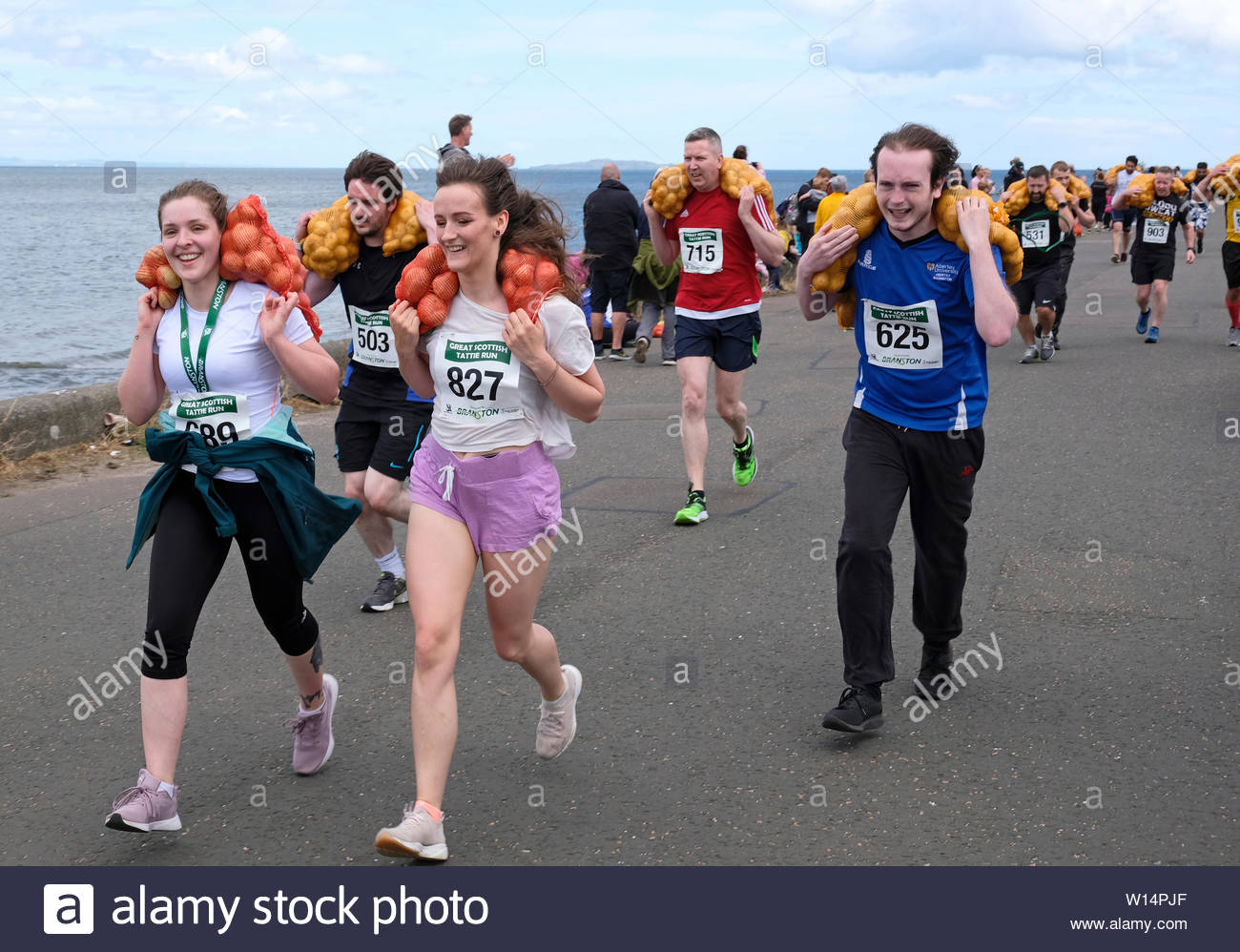 Edinburgh, Scotland, UK. 30th June 2019.  The Great Scottish Tattie Run at Silverknowes Promenade, organised by Great Scottish Events, a fundraising event organiser group. The Race is for one mile with a bag of potatoes 20 kilo for men,10 kilo for women. All participants get to keep their bag of tatties. Credit:Craig Brown - Stock Image