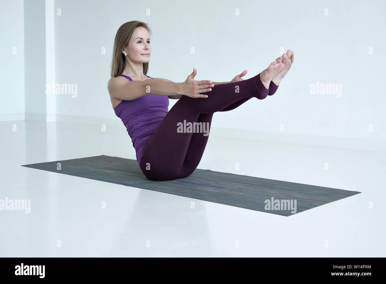 Woman practicing yoga, doing Paripurna Navasana exercise, boat pos - Stock Image