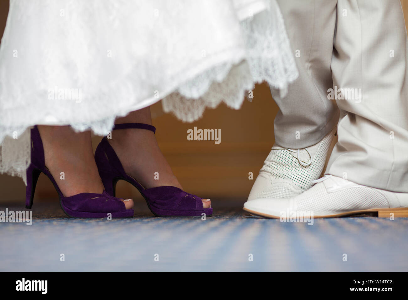 Legs Of The Groom In White Shoes And Trousers And Brides In Purple