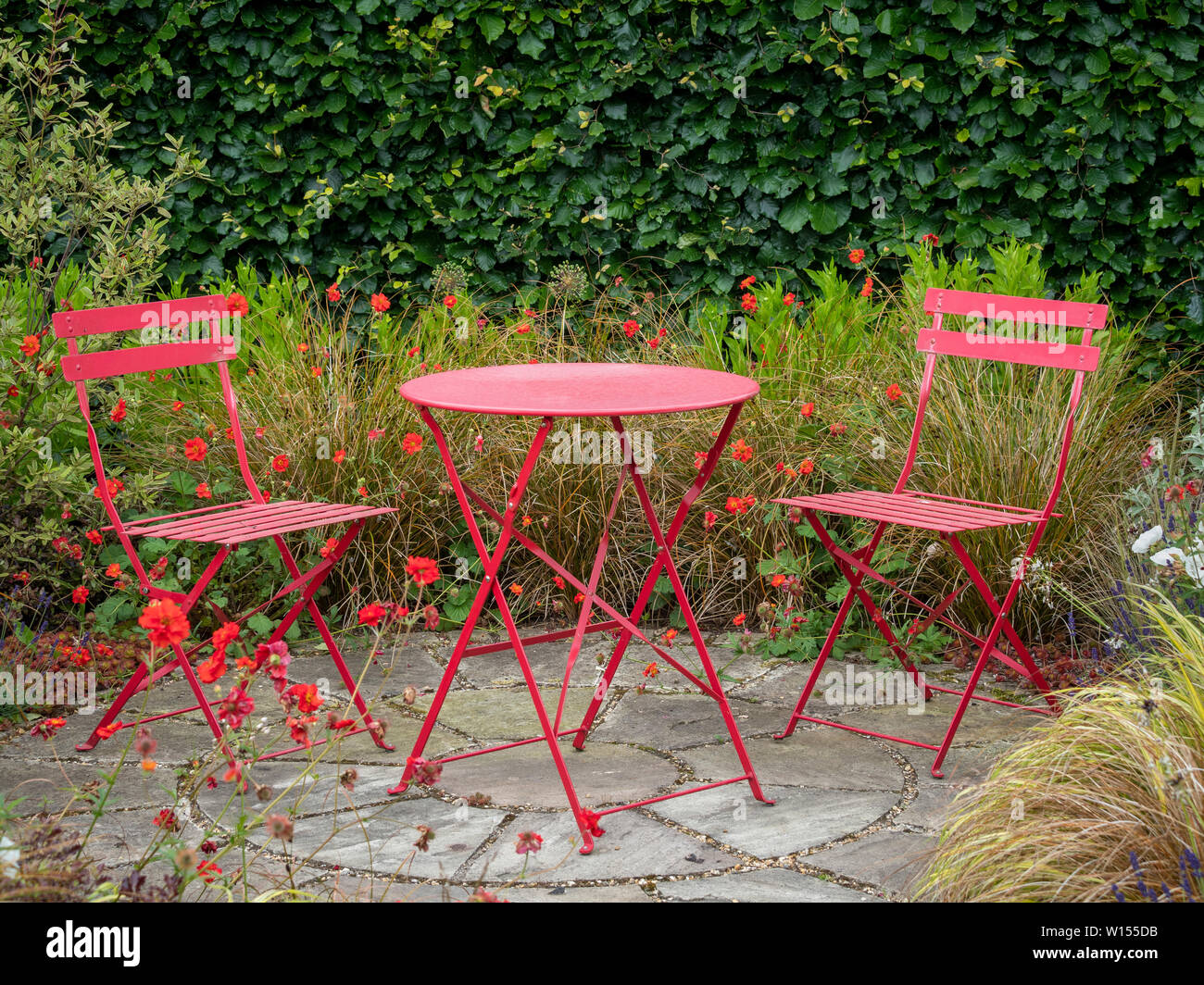 Picture of: Secluded Area Of Garden With Small Patio And Two Red Chairs With Metal Table Surrounded By Summer Flowers And Grasses Stock Photo Alamy