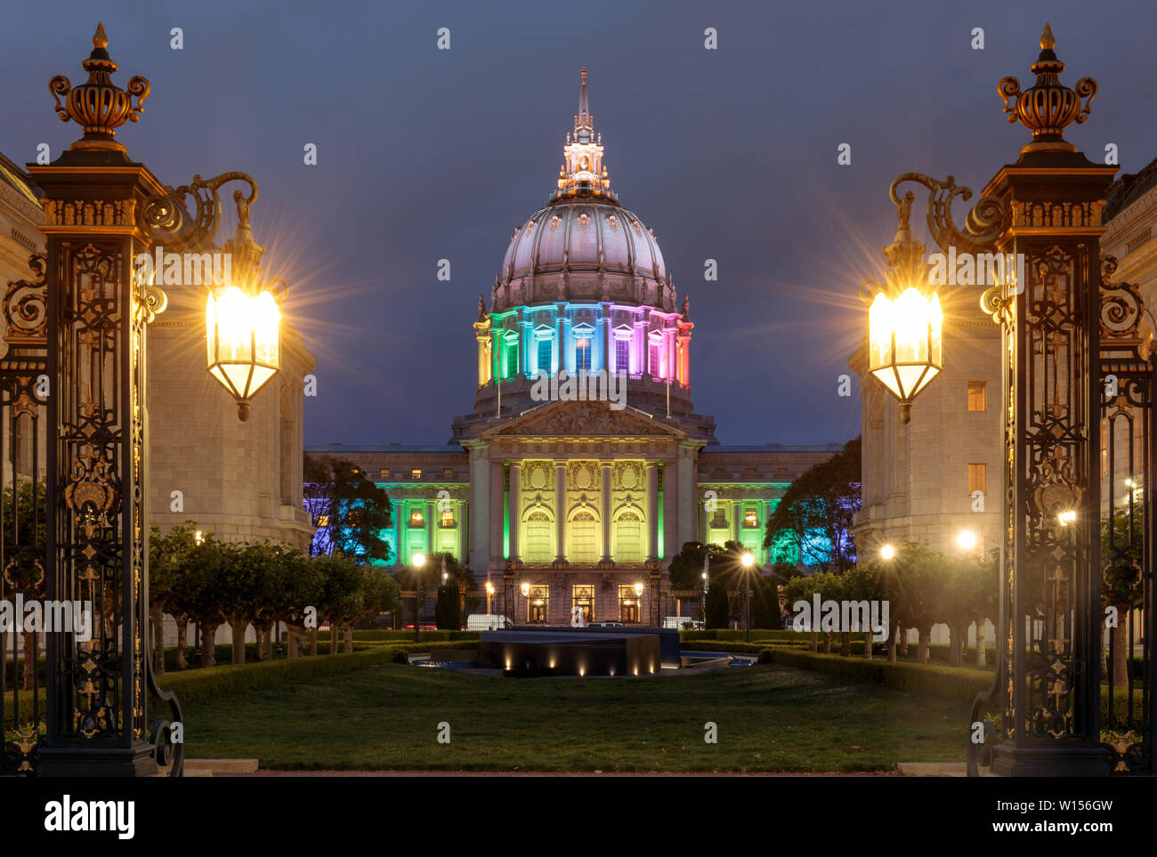 Dusk over San Francisco City Hall illuminated in rainbow colors for the Pride Festival. - Stock Image