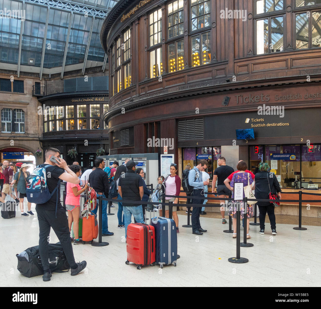Passengers queuing in and standing around the ticket selling office in Glasgow Central Station, Scotland - Stock Image