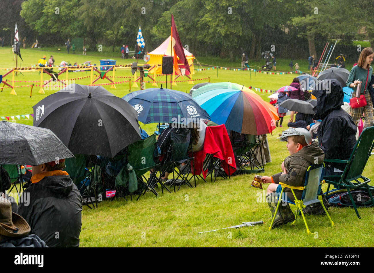 Linlithgow Palace, West Lothian, Scotland, UK. 30th June 2019.  UK Weather: A heavy rain shower soaked event goers to the jousting at Linlithgow Palace who shelter under brightly coloured umbrellas Stock Photo