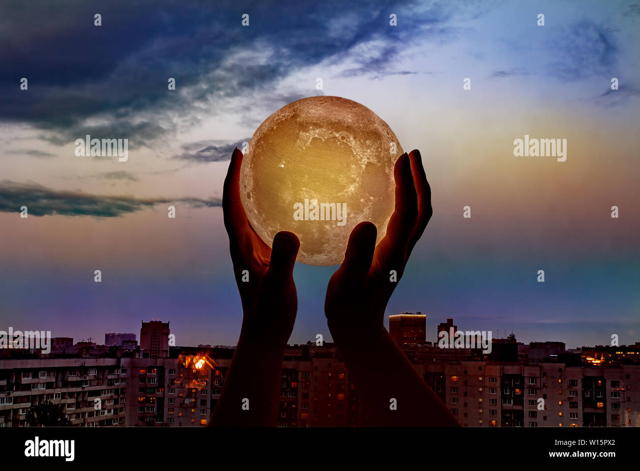 The moon in hands on the background of night city - Stock Image