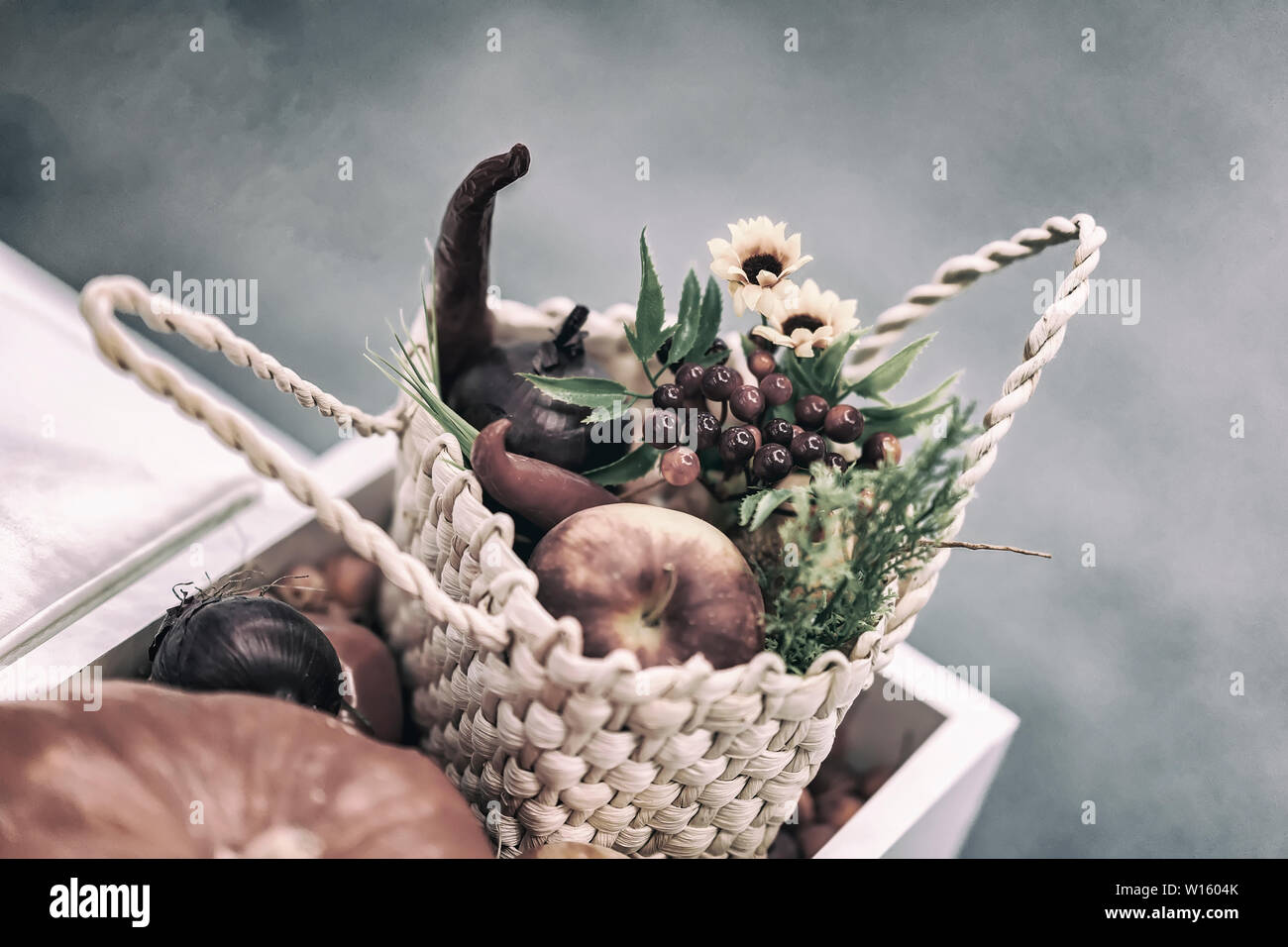 Home festive flower arrangement from leaves, flowers, vegetables, fruits, berries in the rustic wicker basket. Autumn holidays Stock Photo