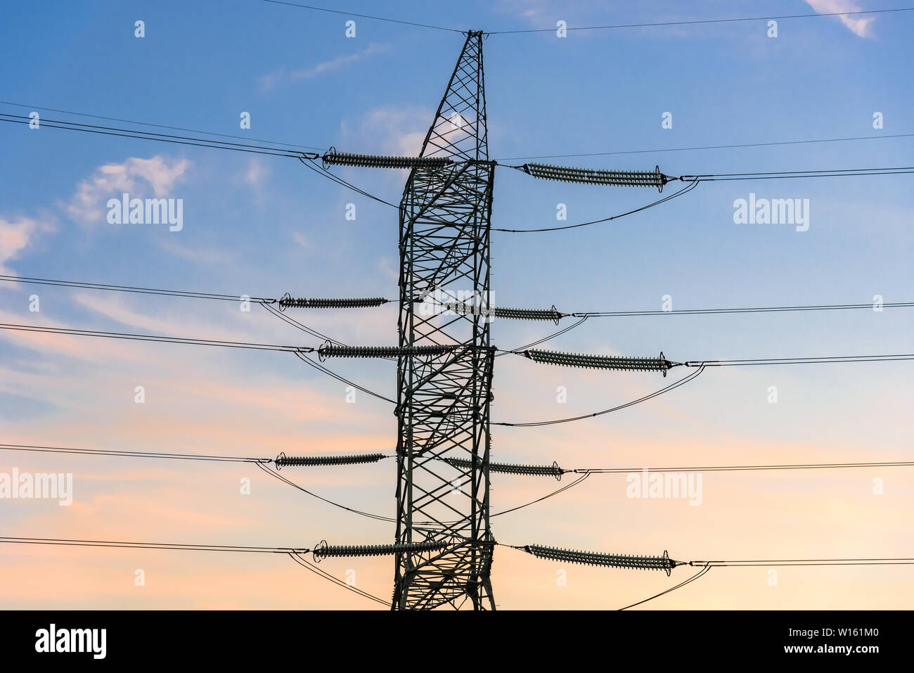 Closeup of electricity pylon and high voltage power lines at sunset Stock Photo