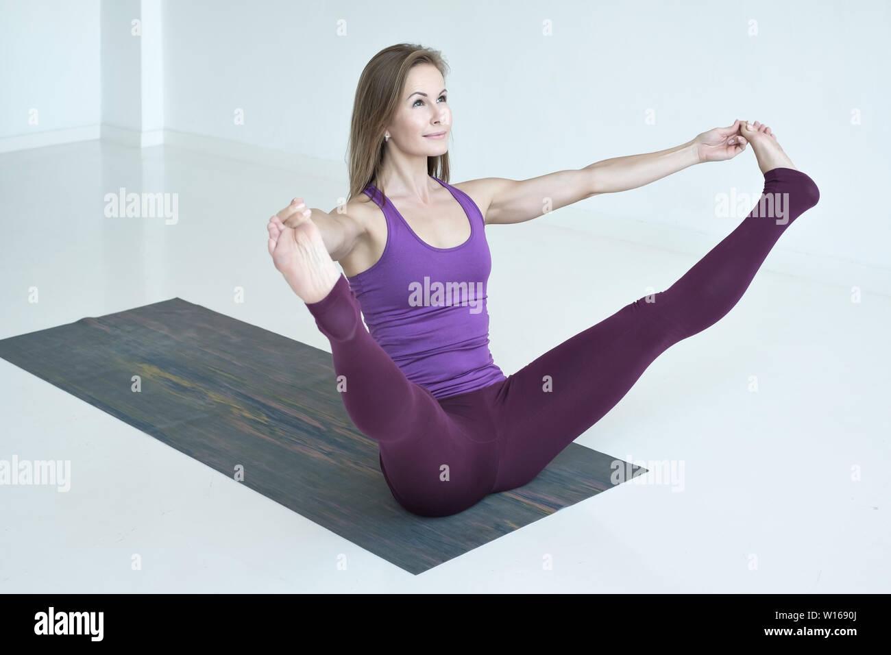 Woman practicing yoga, doing wide legged boat exercise, Prasarita Navasana pose - Stock Image